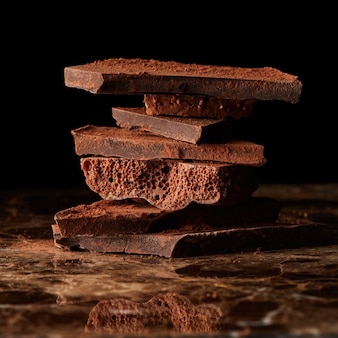Mucchio di pezzi di cioccolato rotti su una superficie di marmo scuro