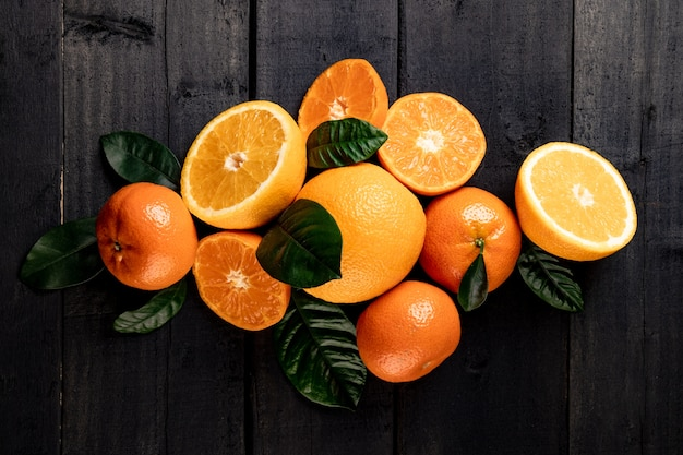 Mucchio di agrumi - arance e mandarini su fondo di legno nero. foto di alta qualità