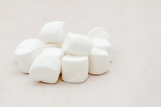 Mucchio di marshmallow lanuginosi bianchi deliziosi su fondo di legno. concetto di sfondo cibo invernale.