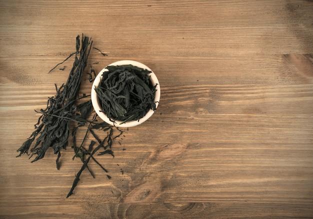 Mucchio di alghe wakame a secco su sfondo di legno. alimento sano di alghe con posto per il testo
