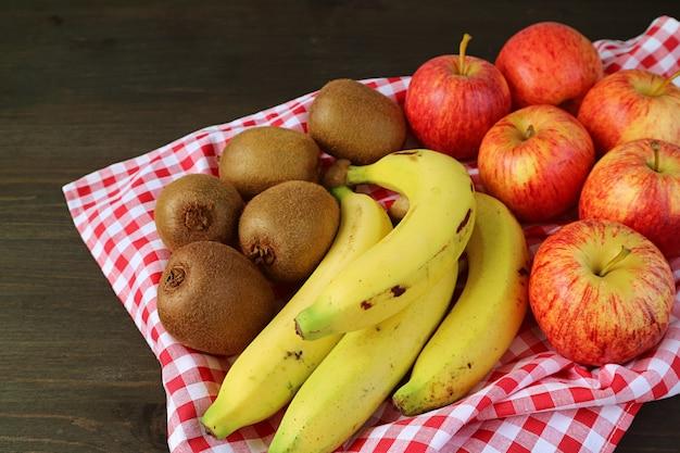 Mucchio di kiwi maturi freschi, banane e mele su un vassoio con panno a scacchi