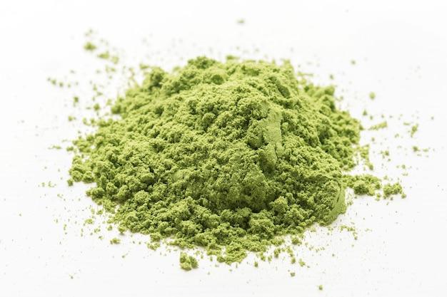Un mucchio di polvere di tè matcha verde su un bianco isolato