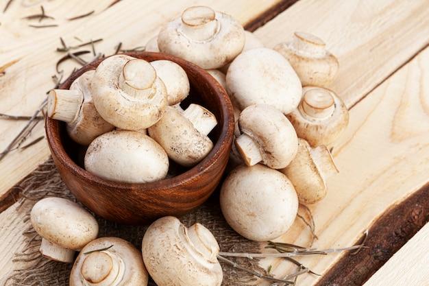 Cumulo di funghi, funghi prataioli nella ciotola sul tavolo di legno, vista dall'alto