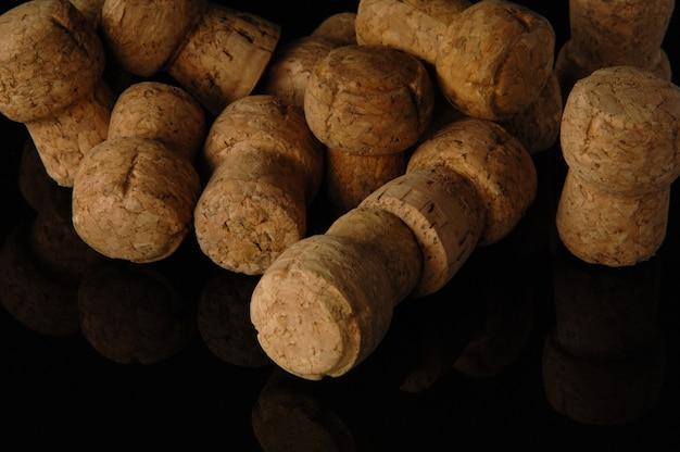 Mucchio di vecchi tappi per vino su sfondo nero con riflesso
