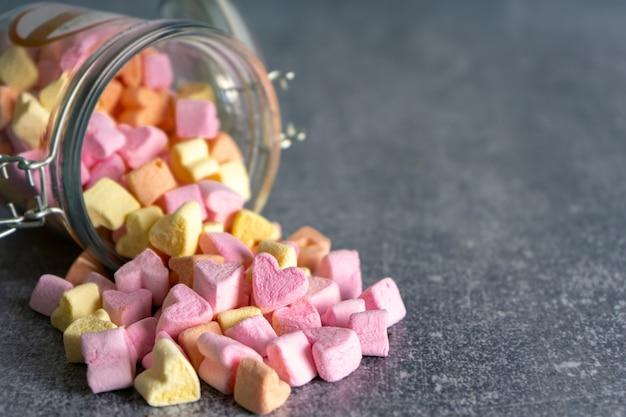 Mucchio di caramelle marshmallow a forma di cuore colorato rosa e giallo sparsi da un barattolo di vetro su sfondo grigio con spazio di copia