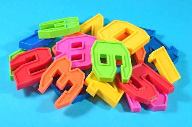 Mucchio di numeri colorati di plastica su uno sfondo blu da vicino