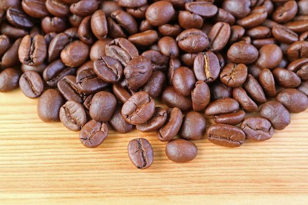 Mucchio di chicchi di caffè tostati su legno