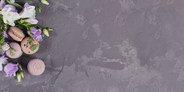 Mucchio di macarons francesi dolci mescolati con fiori su una superficie di cemento grigio. biscotti di amaretti colorati pastello. cibo, cucina, prodotti da forno e concetto di cucina. banner lungo e largo