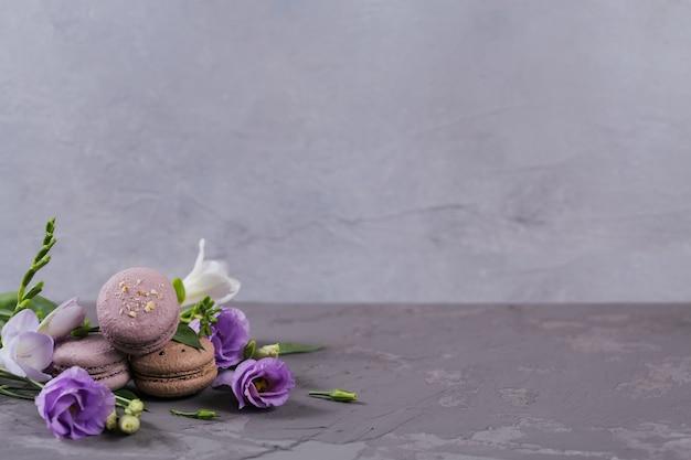 Mucchio di macarons francesi dolci mescolati con fiori su una superficie di cemento grigio. biscotti di amaretti colorati pastello. cibo, cucina, prodotti da forno e concetto di cucina