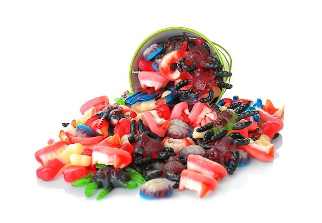 Mucchio di caramelle di gelatina dolce e secchio su sfondo bianco