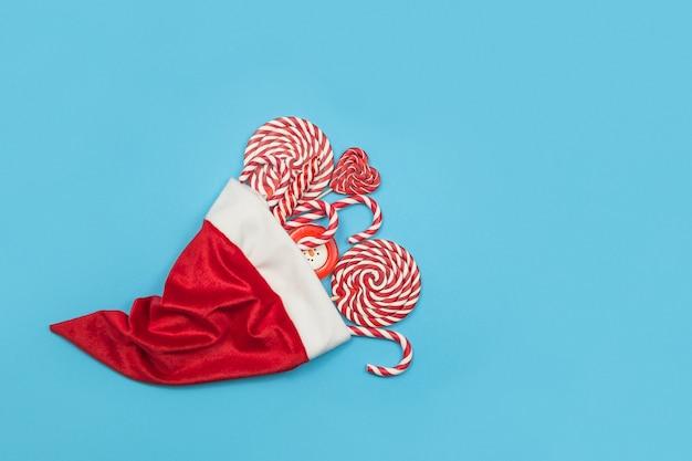 Mucchio di dolci in un cappello di babbo natale. bastoncini di zucchero e lecca-lecca rossi di natale