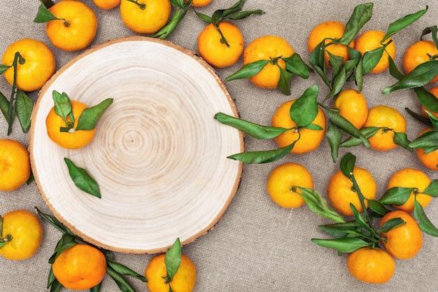 Mucchio di mandarini con foglie verdi su sfondo di tela di sacco. vista dall'alto. lay piatto.