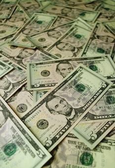 Mucchio delle fatture del dollaro cinque degli stati uniti con il fuoco selettivo e la priorità bassa vaga