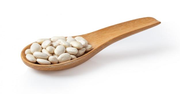 Mucchio dei fagioli bianchi in cucchiaio di legno sulla parete bianca