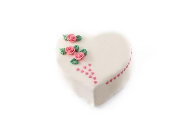 Torta di cuore per san valentino, decorata con rose e cuori di zucchero rosa isolati su sfondo bianco