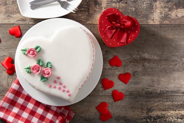 Torta di cuore per san valentino, decorata con rose e cuori di zucchero rosa sulla tavola di legno