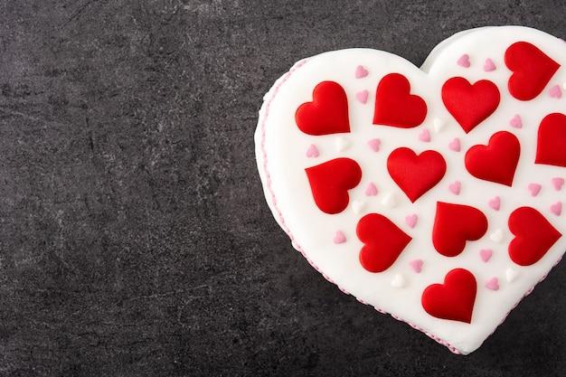 Torta di cuore per il giorno di san valentino, decorata con cuori di zucchero su sfondo nero ardesia