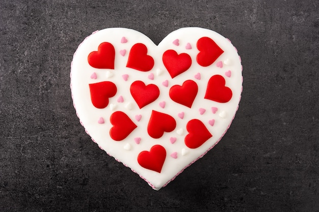 Torta di cuore per san valentino, decorata con cuori di zucchero sulla superficie dell'ardesia nera