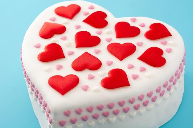Torta cuore per san valentino, decorata con cuori di zucchero su sfondo blu