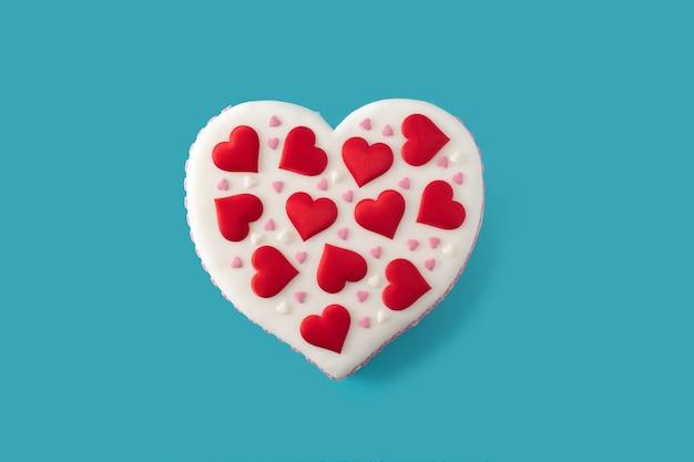 Torta cuore per san valentino, decorata con cuori di zucchero su superficie blu