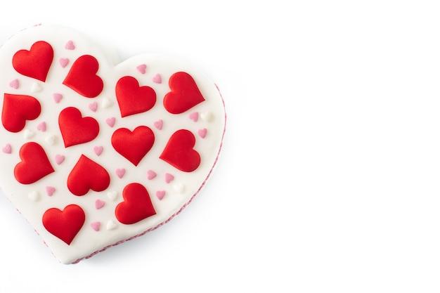 Torta di cuore per il giorno di san valentino, decorata con cuori di zucchero isolati su sfondo bianco
