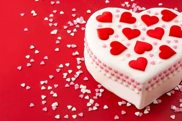 Torta cuore per san valentino, decorata con cuori di zucchero su sfondo rosso