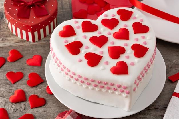 Torta di cuore per san valentino, decorata con cuori di zucchero sulla tavola di legno
