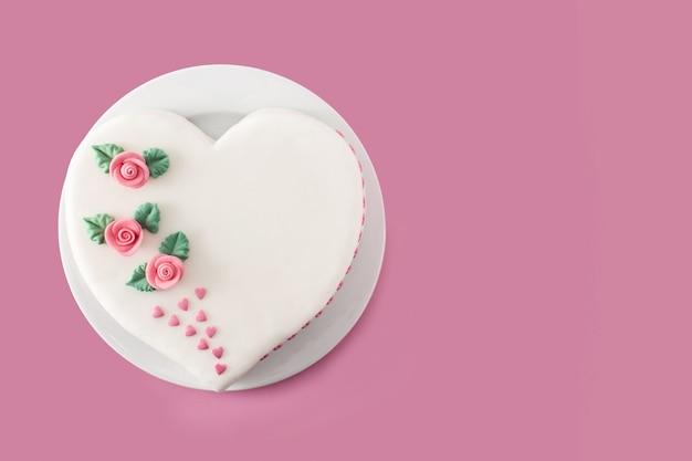 Torta cuore per san valentino, festa della mamma o compleanno, decorata con rose e cuori di zucchero rosa su sfondo rosa