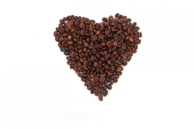 Cuore di chicchi di caffè su uno spazio bianco