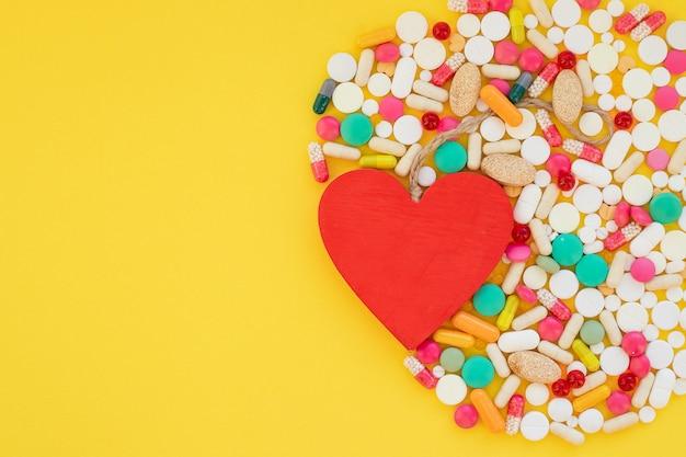 Cuore e pillole colorate su giallo
