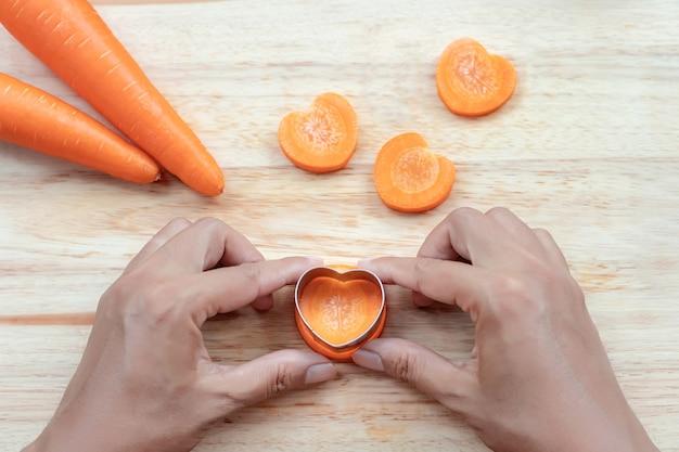 Lavorazione del cuore sulla carota con le mani che premono. timbro di verdure in alluminio a forma di cuore.
