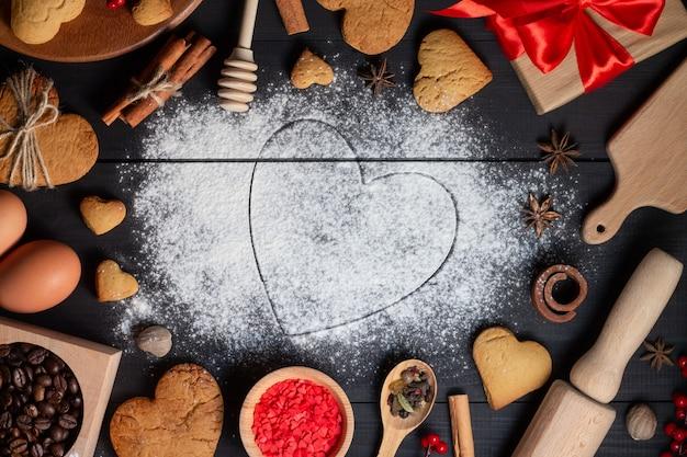 Cuore disegnato sulla farina. biscotti di panpepato, spezie, chicchi di caffè e prodotti da forno.