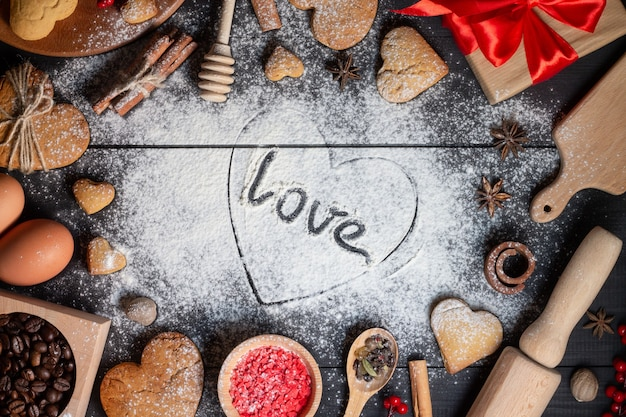 Cuore disegnato sulla farina con la scritta love. biscotti di panpepato, spezie, chicchi di caffè e prodotti da forno su fondo di legno nero
