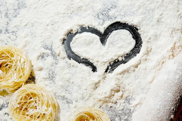 Cuore di farina e mattarello su sfondo nero. vista dall'alto, copia spazio