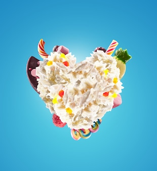 Forma di cuore da panna montata con dolci, gelatine, vista frontale del cuore. tendenza alimentare pazza di freakshake. il cuore spezzato di panna, pieno di caramelle ai frutti di bosco e gelatina, concetto di caramelle al cioccolato.
