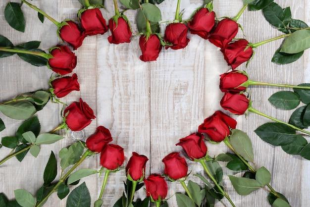 Cornice cuore fatta di rose su uno sfondo di legno