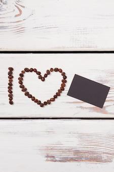 Chicchi di caffè a forma di cornice di cuore e carta nera vuota. amo copyspace. plance di legno bianche.