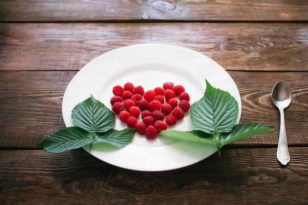 Cuore di lampone con decorazioni di foglie sul piatto