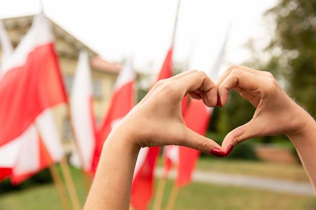 Gesto del cuore con le bandiere della polonia dietro