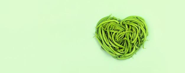Cuore di fagiolini su sfondo verde, vista dall'alto.