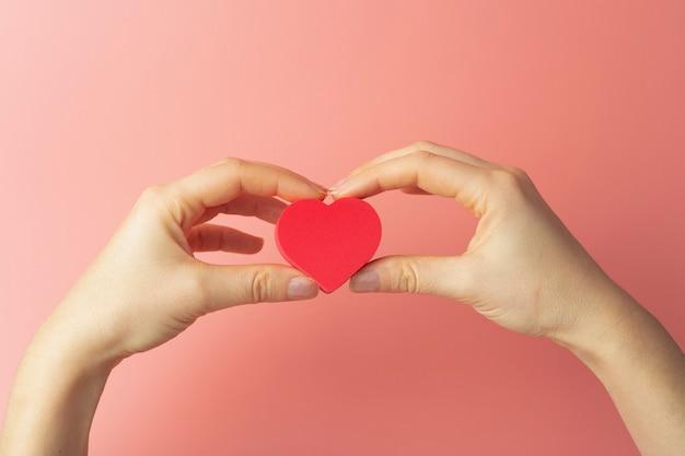 Cuore nelle mani di una donna su uno sfondo colorato. sfondo per san valentino (14 febbraio) e amore.