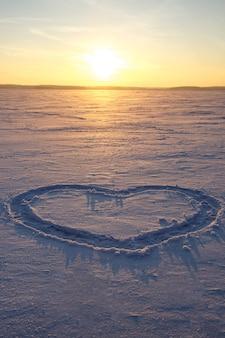 Un cuore è disegnato nella neve. tramonto sullo sfondo.