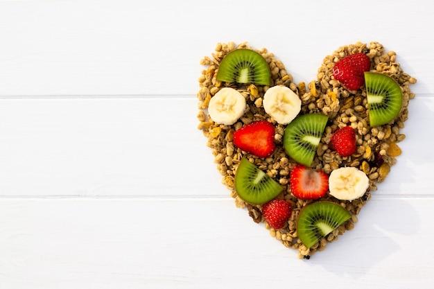 Cuore di cui muesli e frutta su uno sfondo di legno bianco. lay piatto. copia spazio.