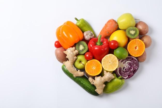 Cuore presentato dalle verdure e dalla frutta su bianco