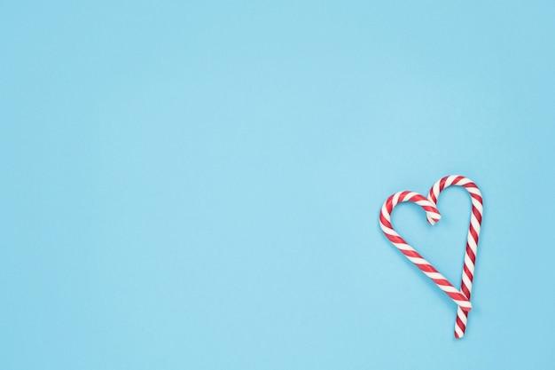 Cuore fatto di bastoncini di zucchero su sfondo blu. il minimo concetto di amore
