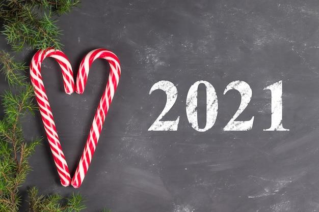 Cuore fatto di bastoncini di caramelle su uno sfondo di gesso con rami di abete con la scritta 2021