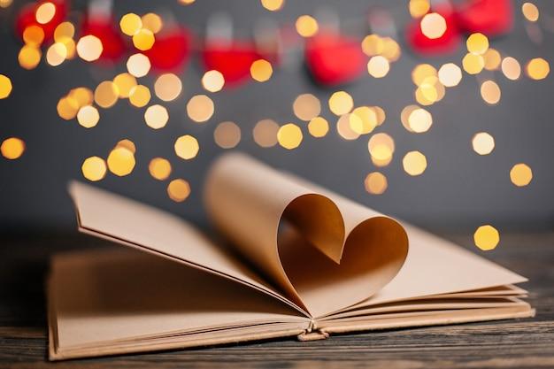 Cuore fatto da fogli di libri in luci, amore e concetto di san valentino su un tavolo di legno
