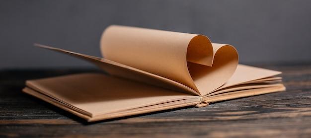 Cuore fatto da fogli di libri, amore e concetto di san valentino su un tavolo di legno