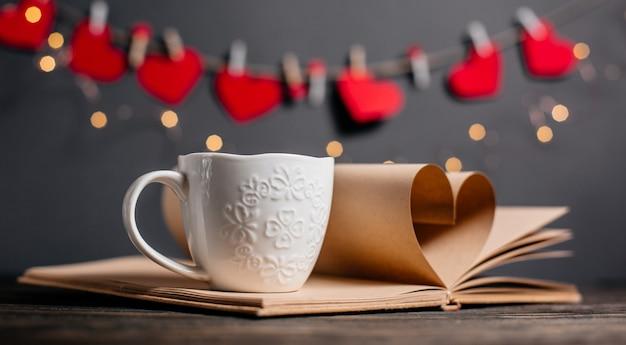 Cuore fatto da fogli di libri con una tazza di luci, amore e concetto di san valentino su un tavolo di legno