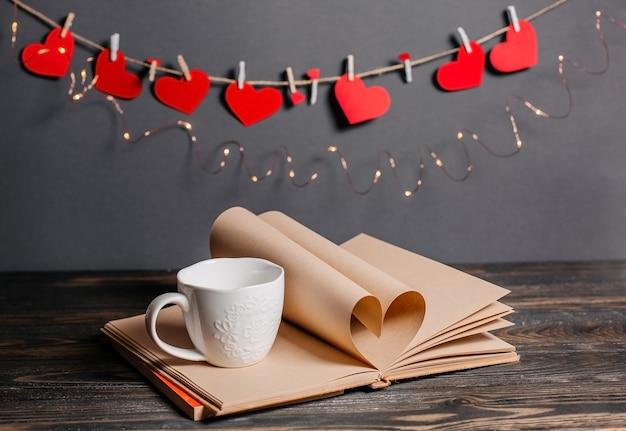 Cuore fatto da fogli di libri con una tazza, l'amore e il concetto di san valentino su un tavolo di legno
